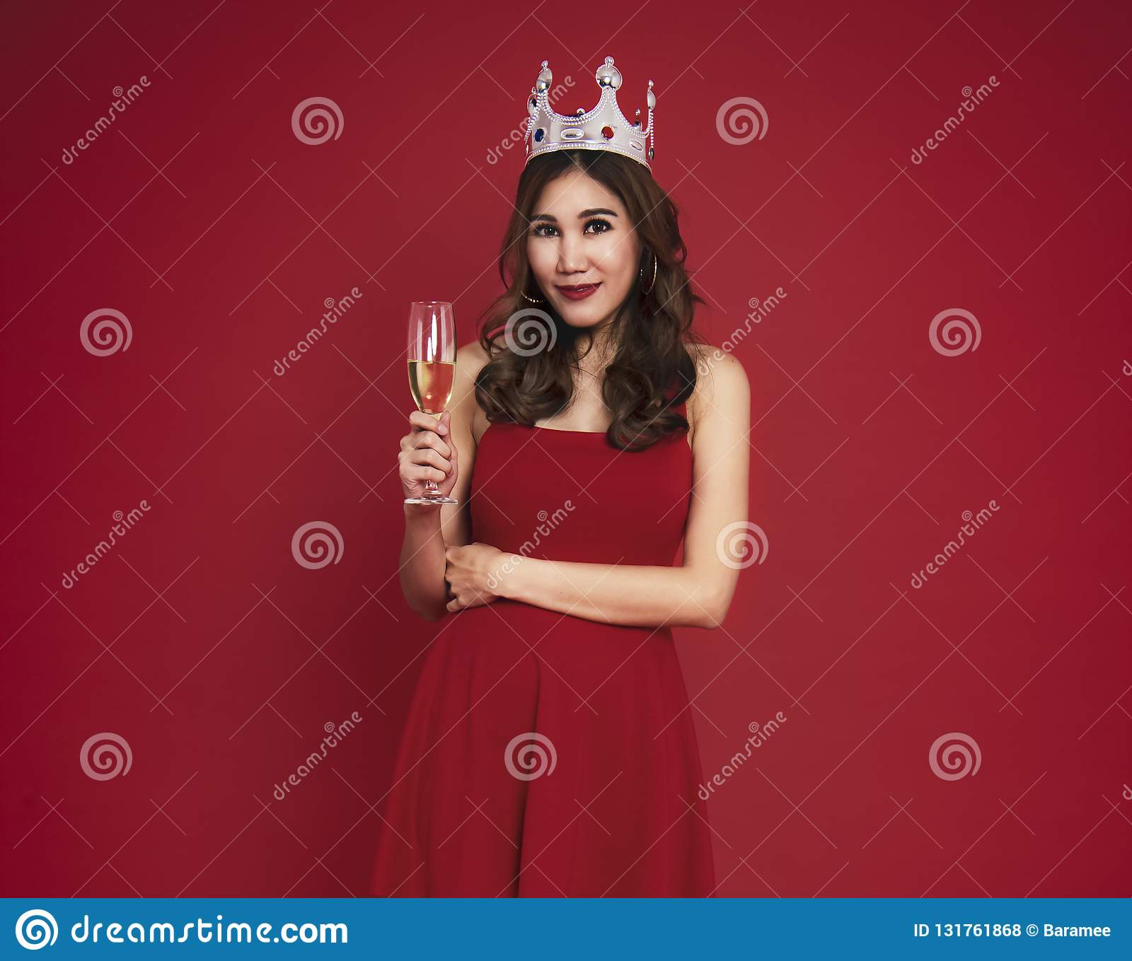 Young woman holding glasses of champagne and smiling while celebrating on red background. christmas and happy new year concept