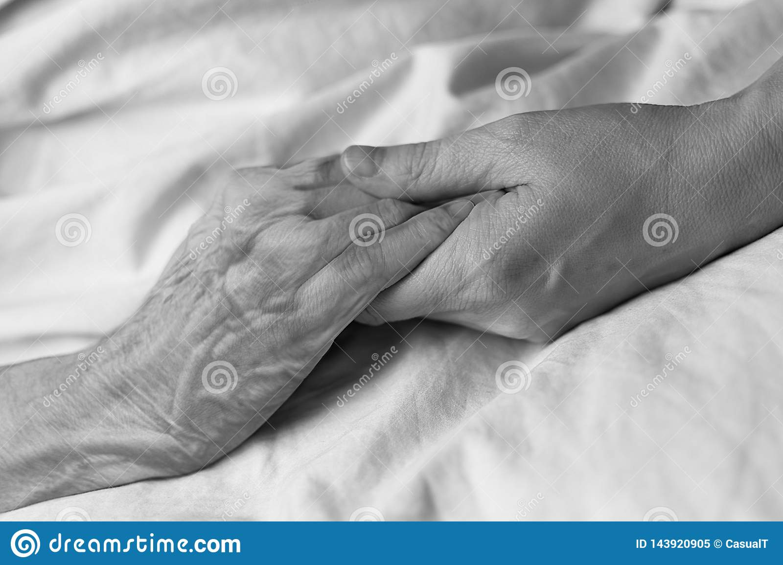 A young woman holding the hand of an old woman in a hospital bed, black & white