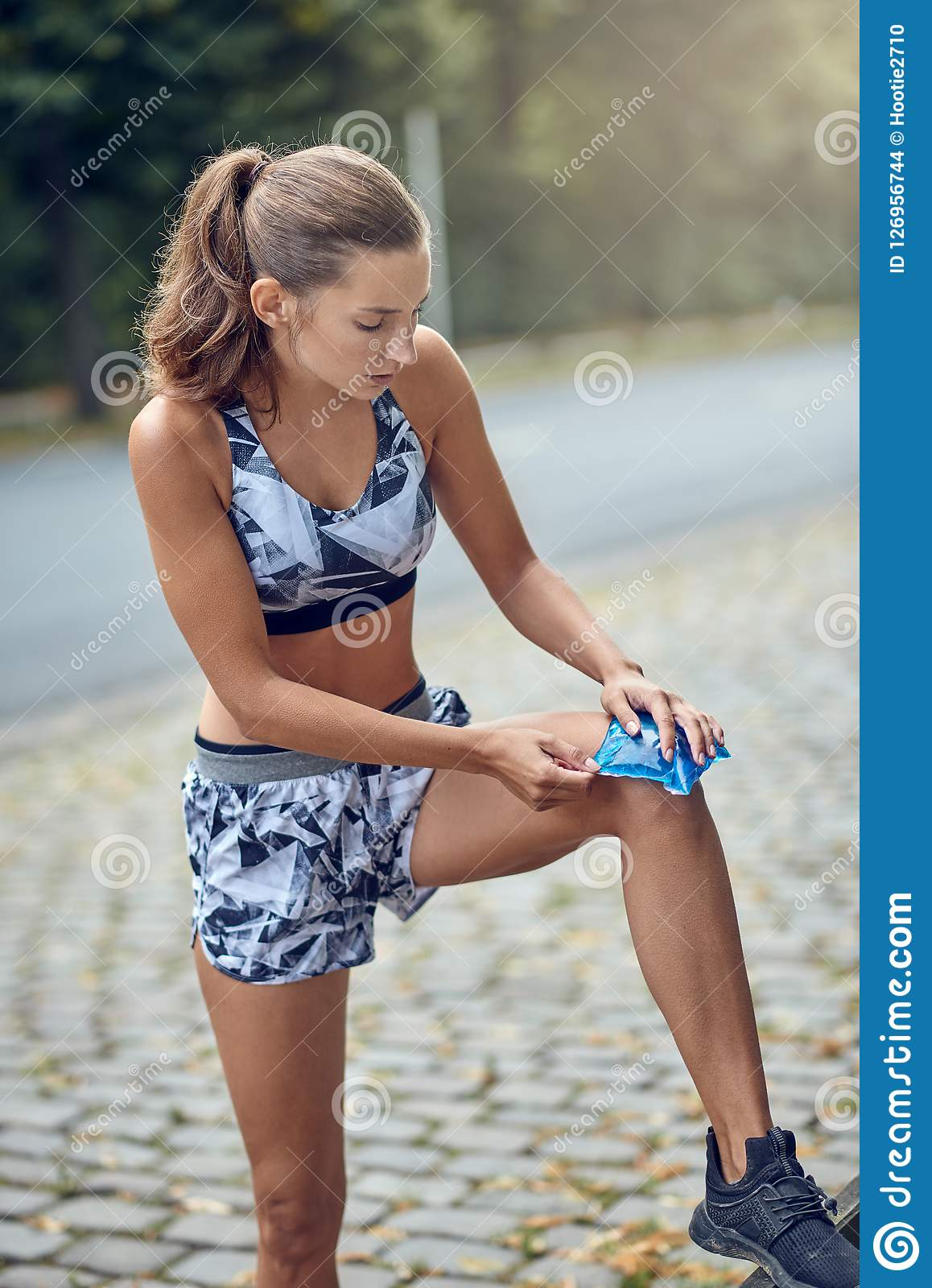 Young woman holding an ice pack to her knee