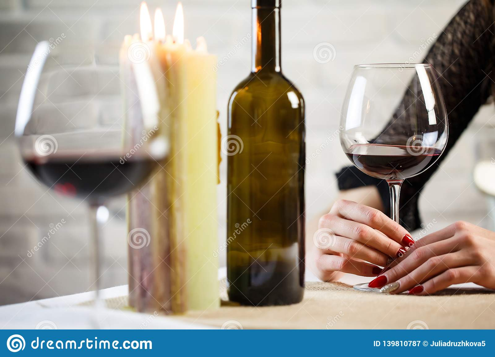 A young woman holds in her hand a glass of wine on a blind date. Two wineglass on the table. Close up