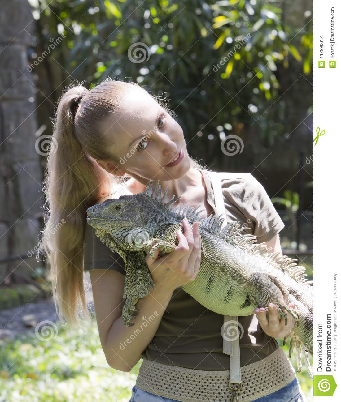 The young woman holds iguana on hands