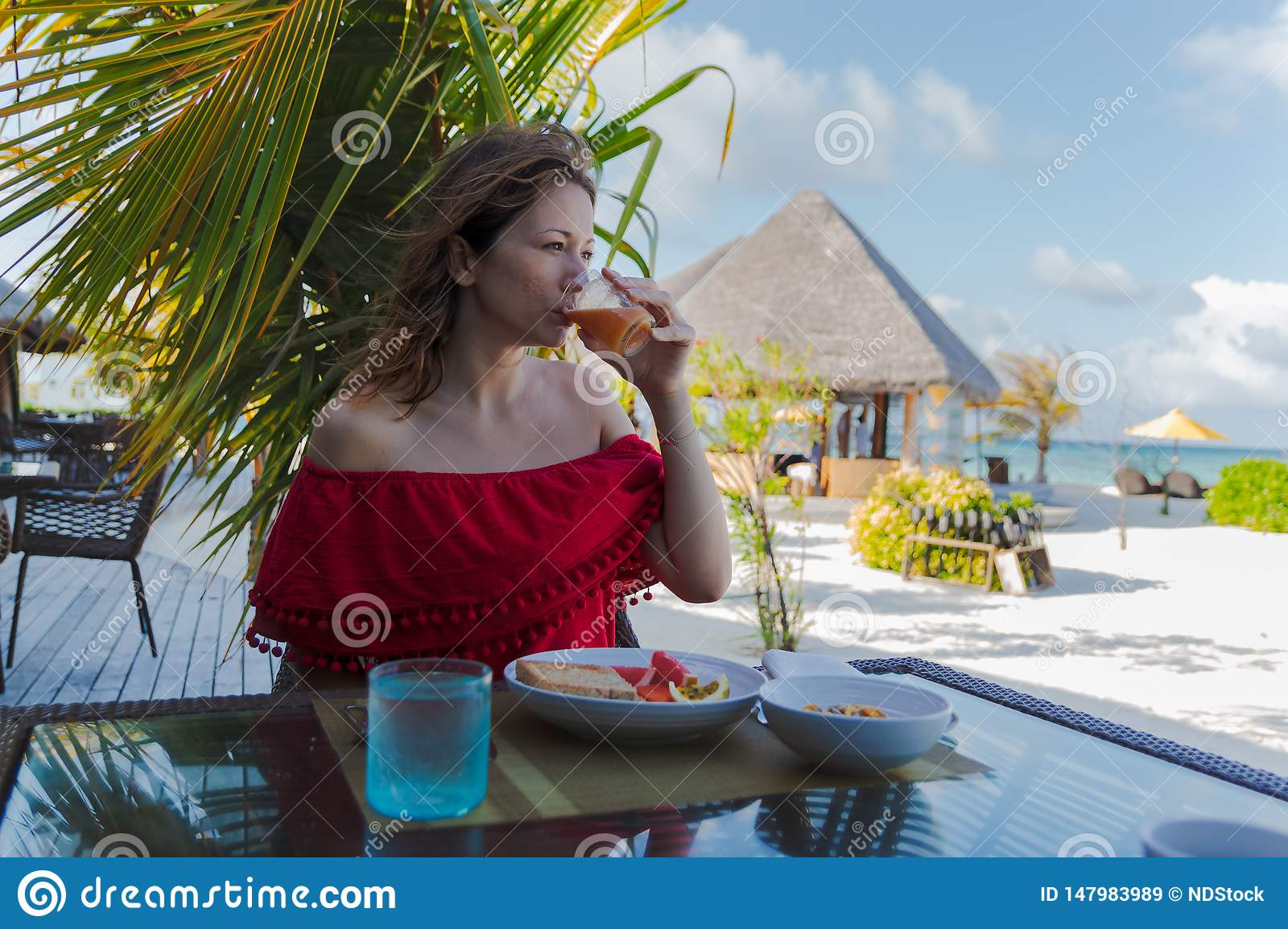 Young woman on holiday in a tropical island eating a healthy breakfast