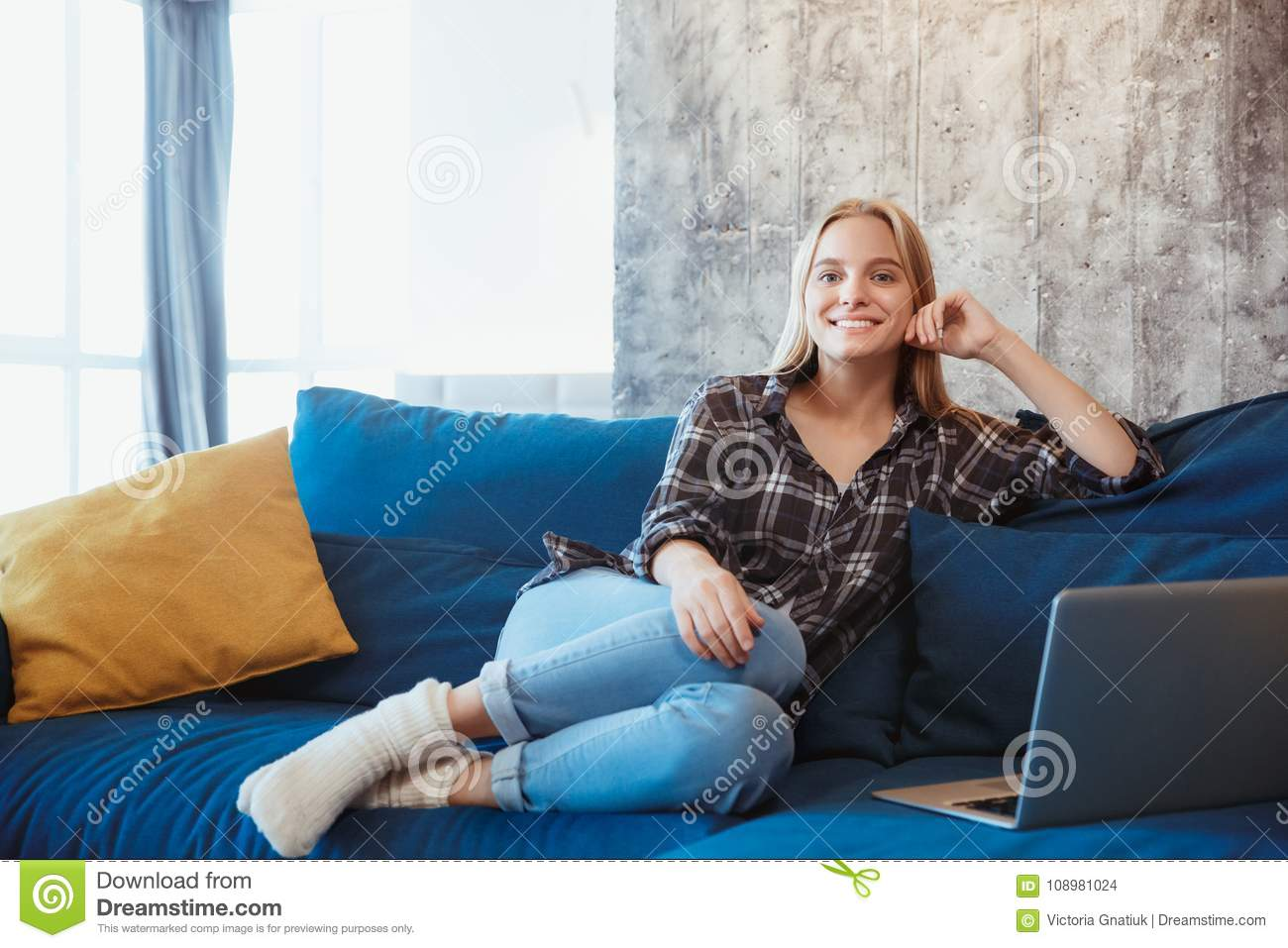 Young woman at home in the living room resting on coach
