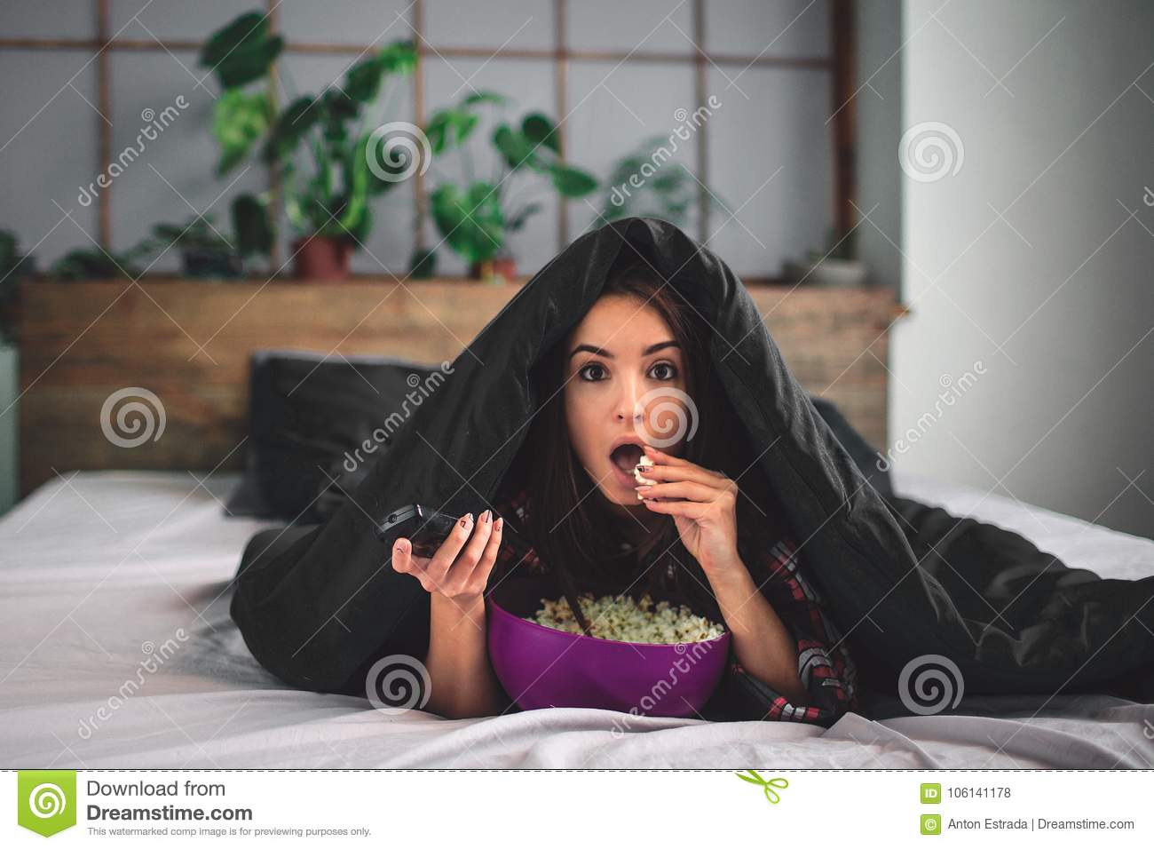 Young woman at home sofa couch in living room watching television scary horror movie or suspense thriller film or