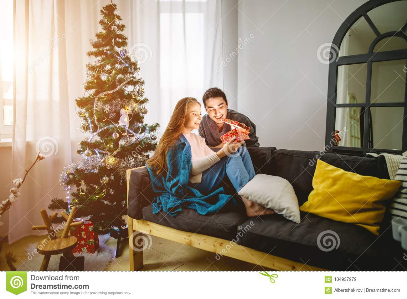 Young Woman With Husband Looking At Christmas Gift Stock Image ...