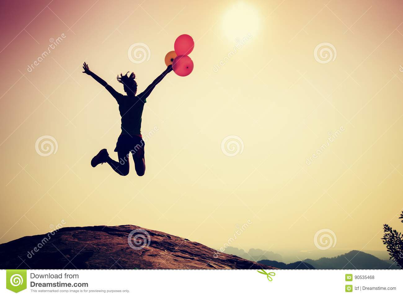 Woman jumping with colorful balloons on sunrise mountain peak