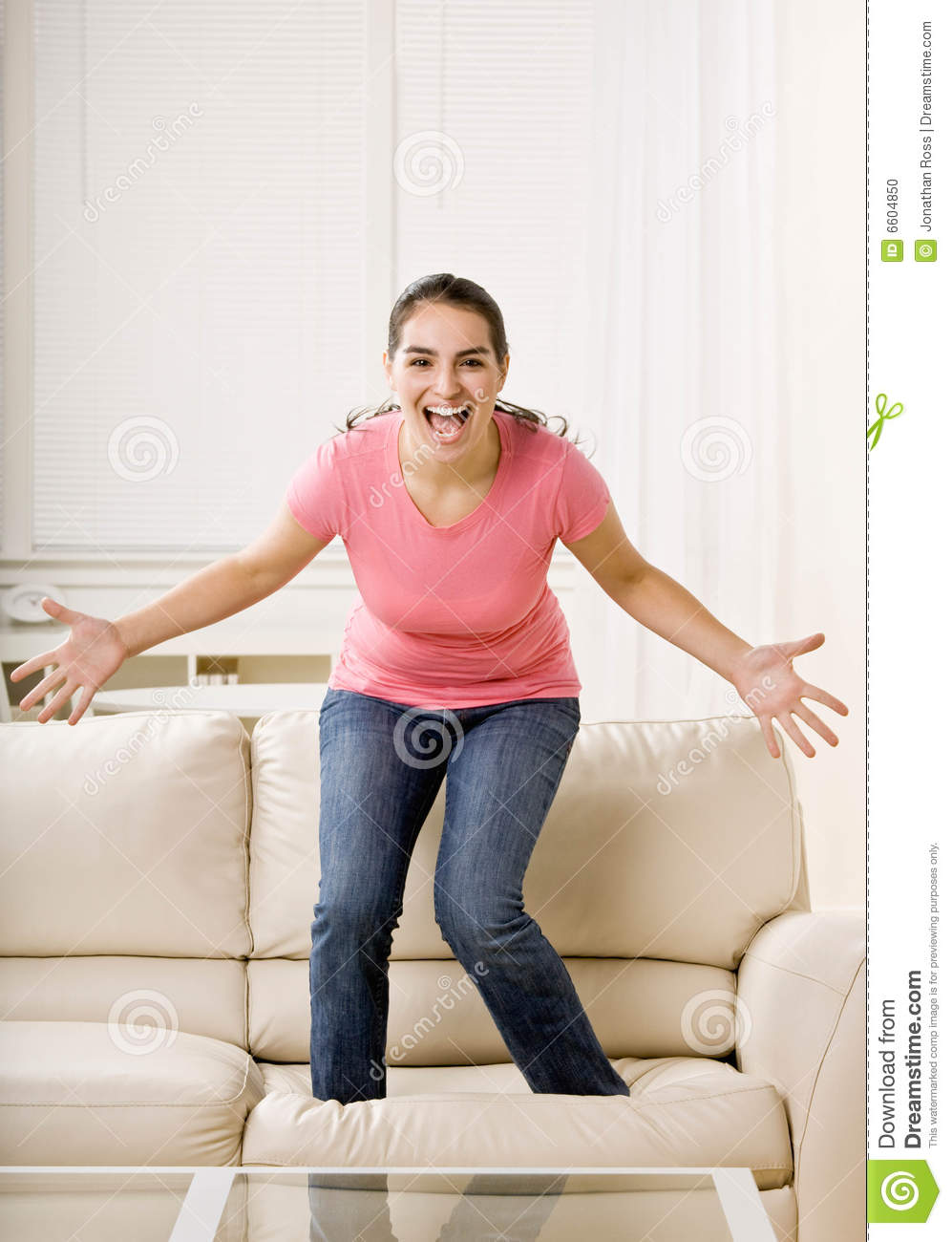 Young Woman Jumping On Couch Stock Photo Image 6604850