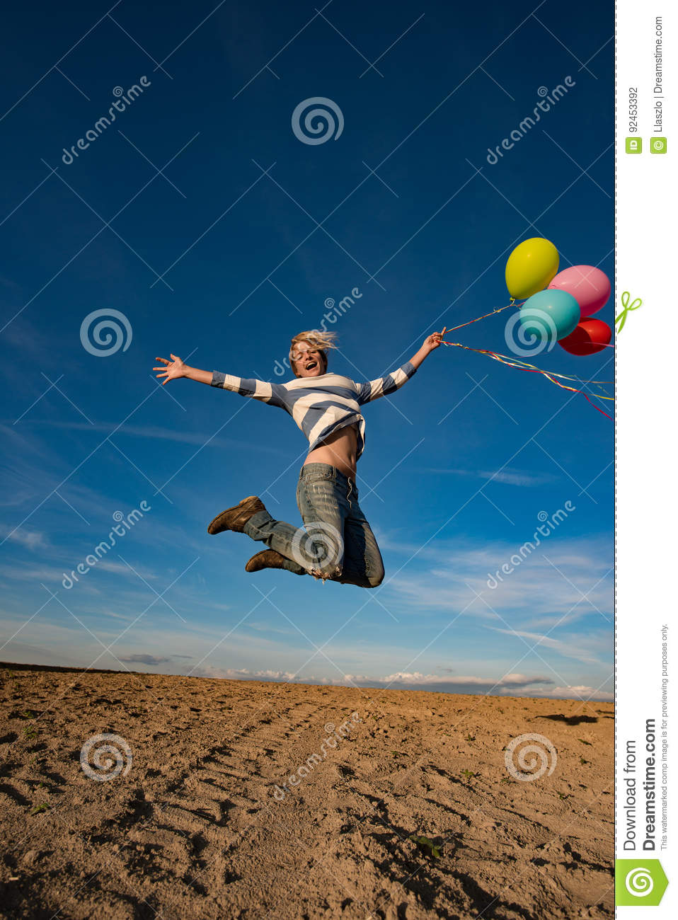 Young woman jumping with toy balloons