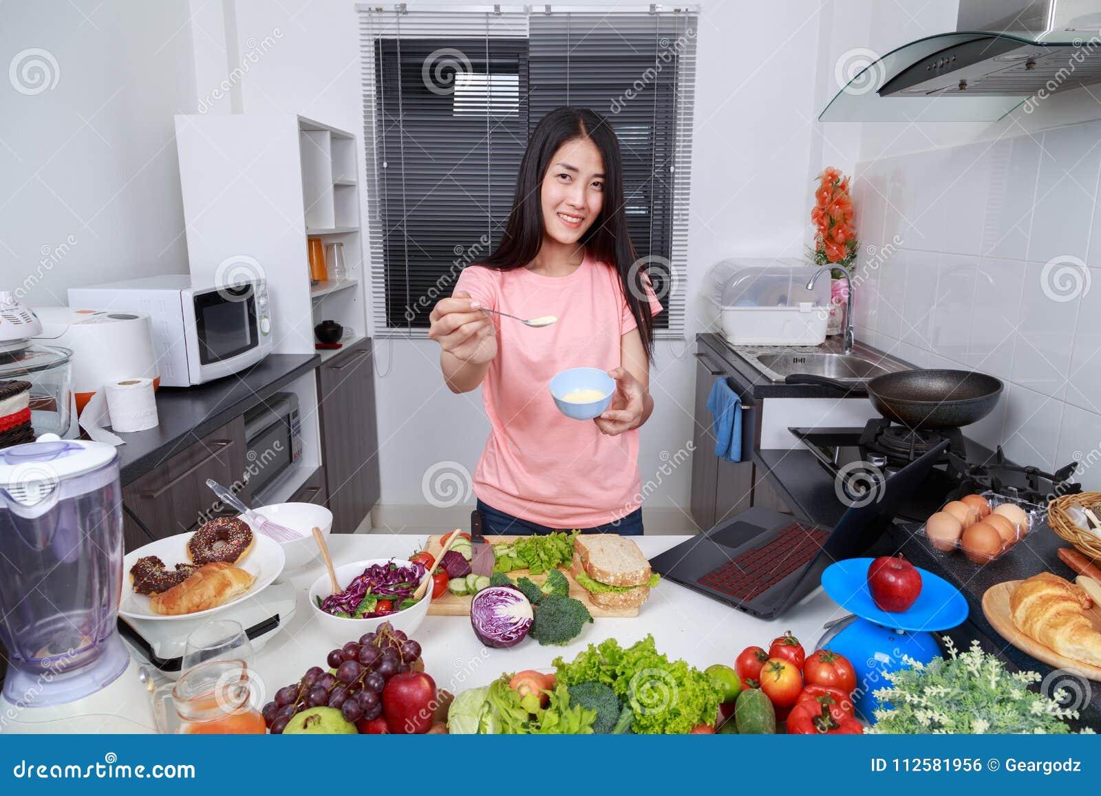 Woman in kitchen preparing salad dressing in bowl