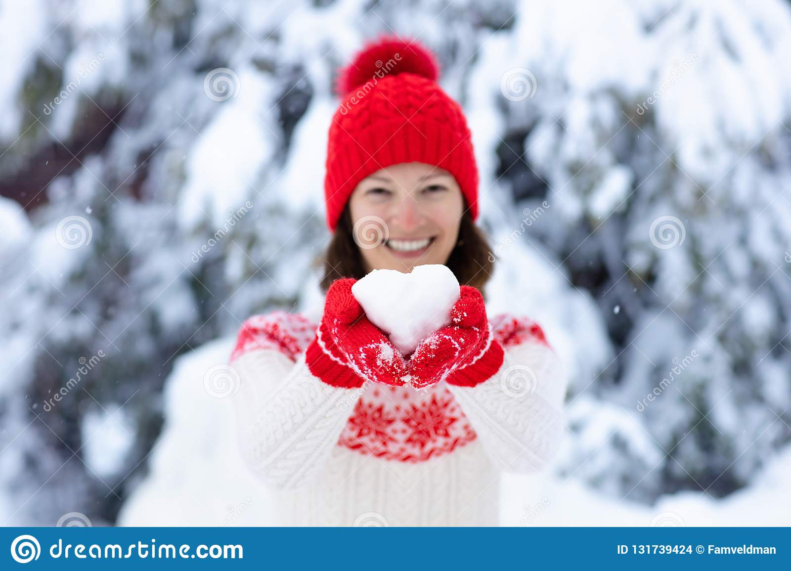 Young woman in knitted sweater holding heart shape snow ball in winter. Girl in family snow fight game. Female in knit handmade