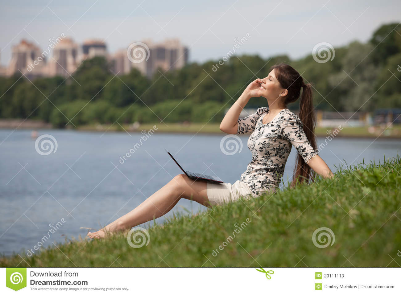 Young woman with laptop and mobile phone in park.