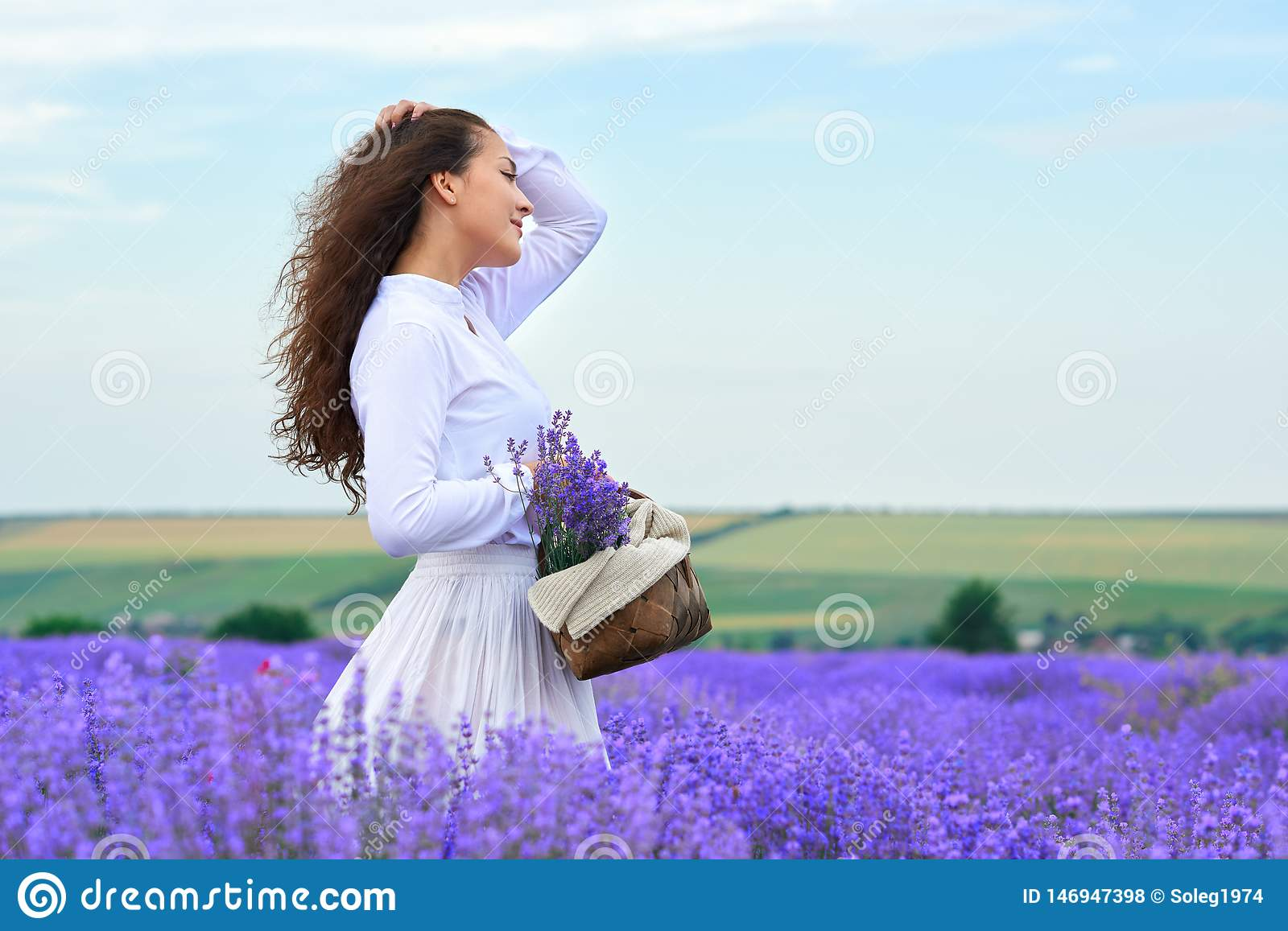 Young woman is in the lavender flower field, beautiful summer landscape