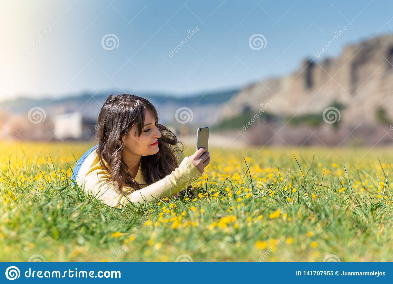Young Woman Laying Down Using Mobile Phone