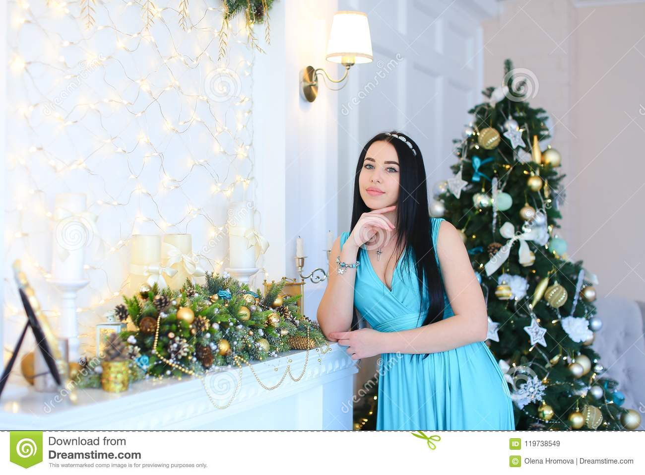 Young woman leaning against decorated fireplace, wearing blue dress and bracelet in Christmas tree background.