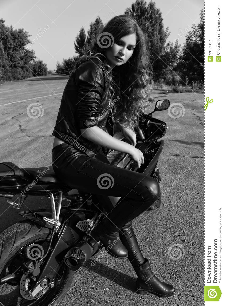 Young woman in leather clothes near a motorcycle black and white photo