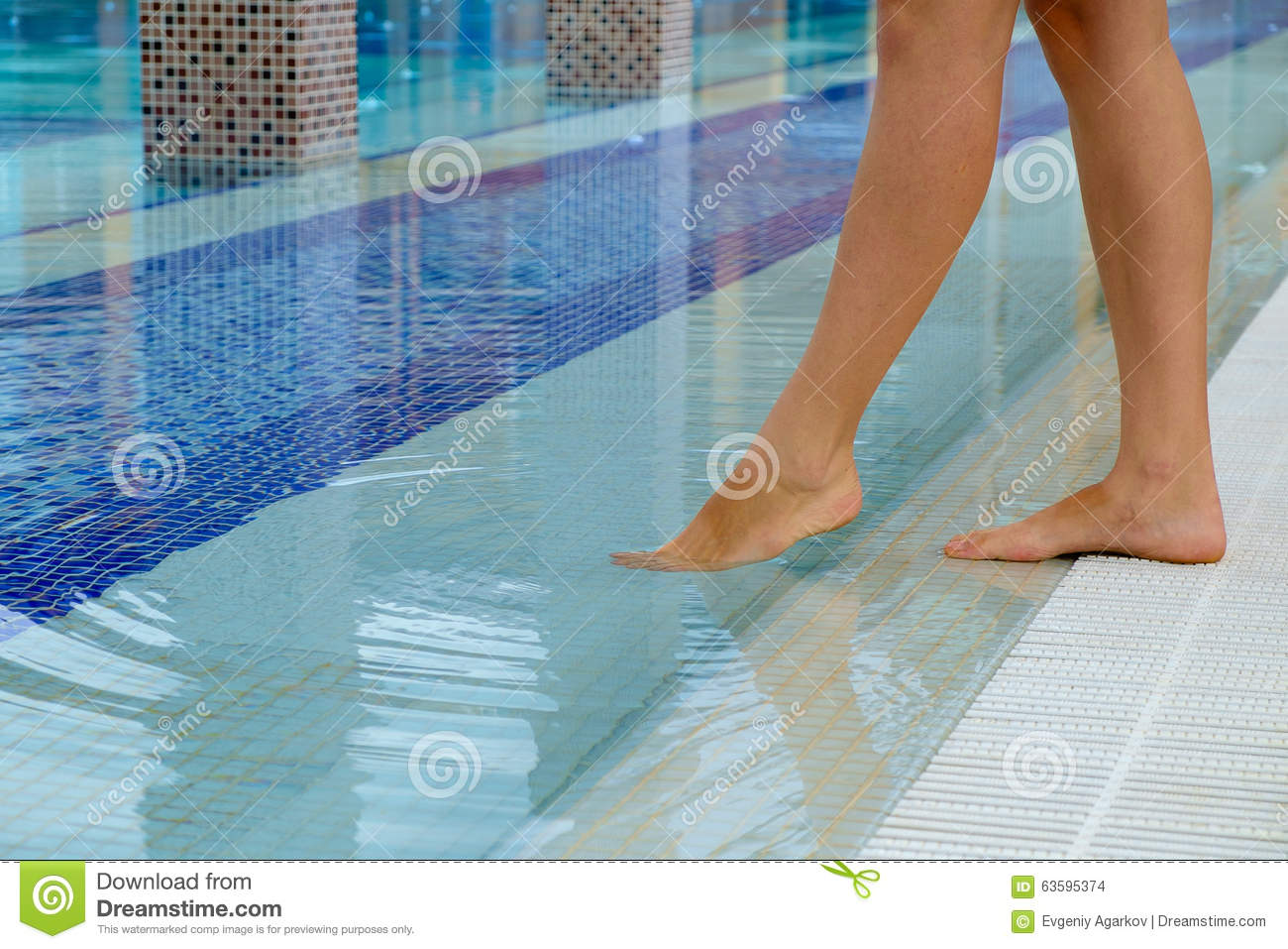 Young woman legs standing on the edge of a swimming pool and tasting the temperature of the for What temperature should a swimming pool be