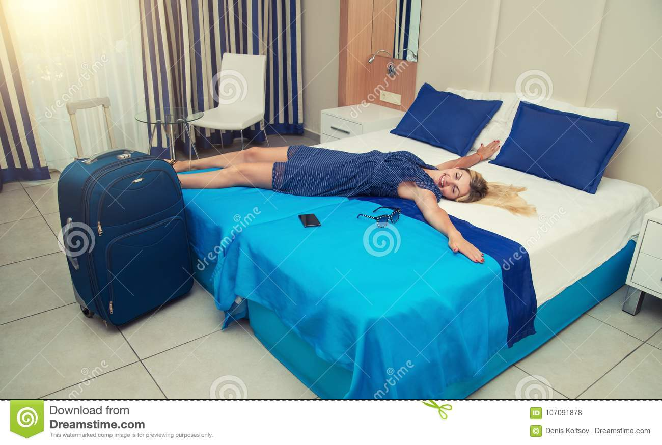 Young woman lies and has a rest on the bed in the hotel room.