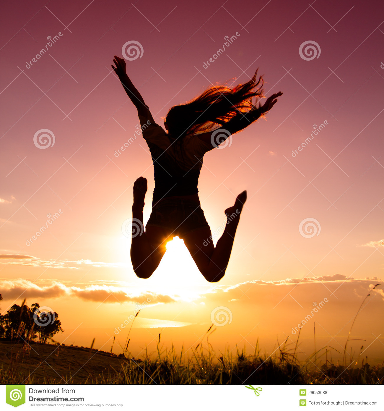 Young woman joyfully jumping with sunset in backround