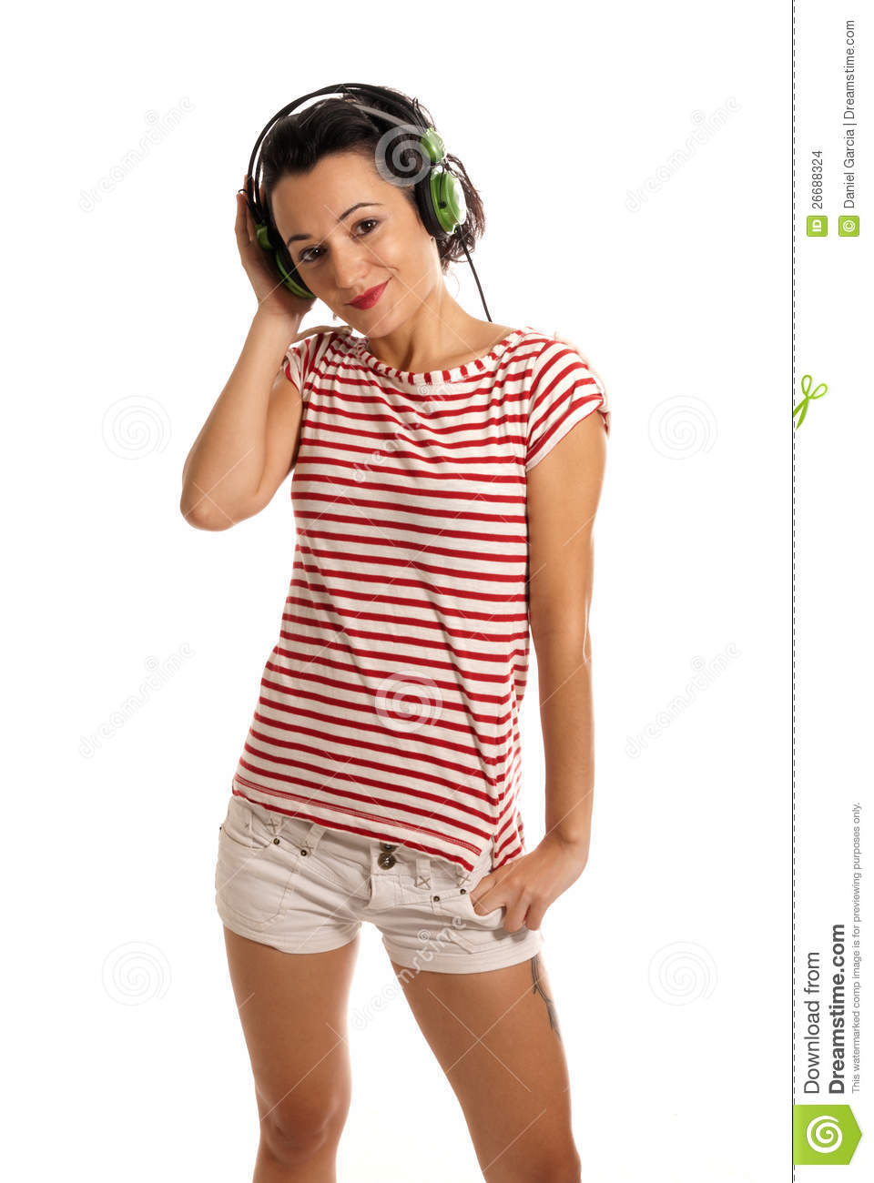 Young woman listening music with headphones standing on white background