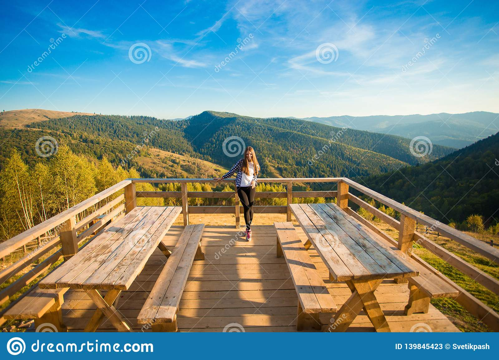 Young woman with long hair on fence of wooden terrace enjoy beautiful view of mountains