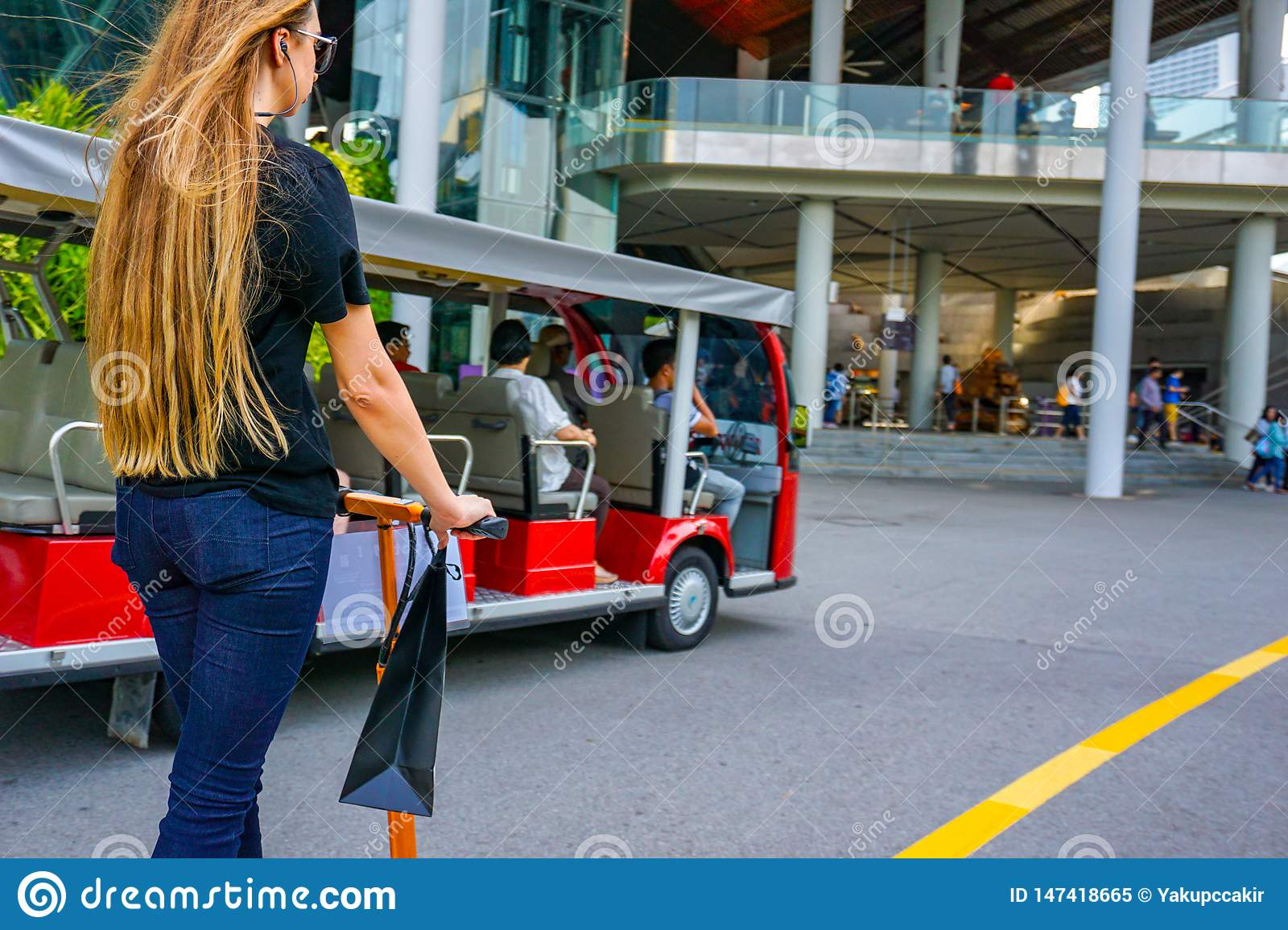 Young woman with long hairs on electric scooter. The girl on the electric scooter drinks coffee.