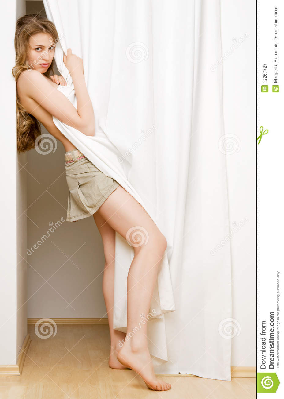 Young Woman Looking From Behind A White Curtain Stock