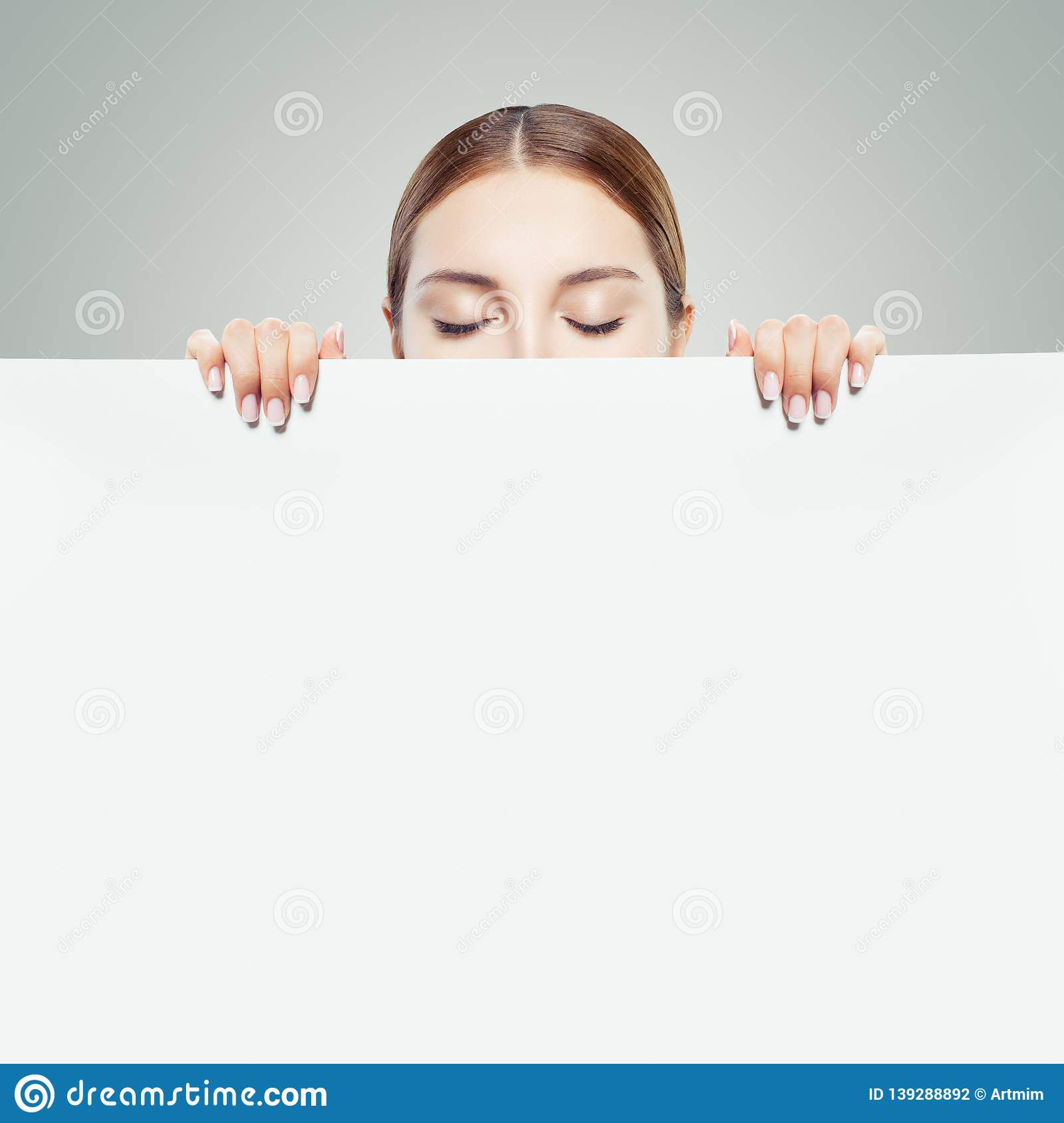 Young woman looking down and showing white empty paper card background with copy space for advertising marketing or product