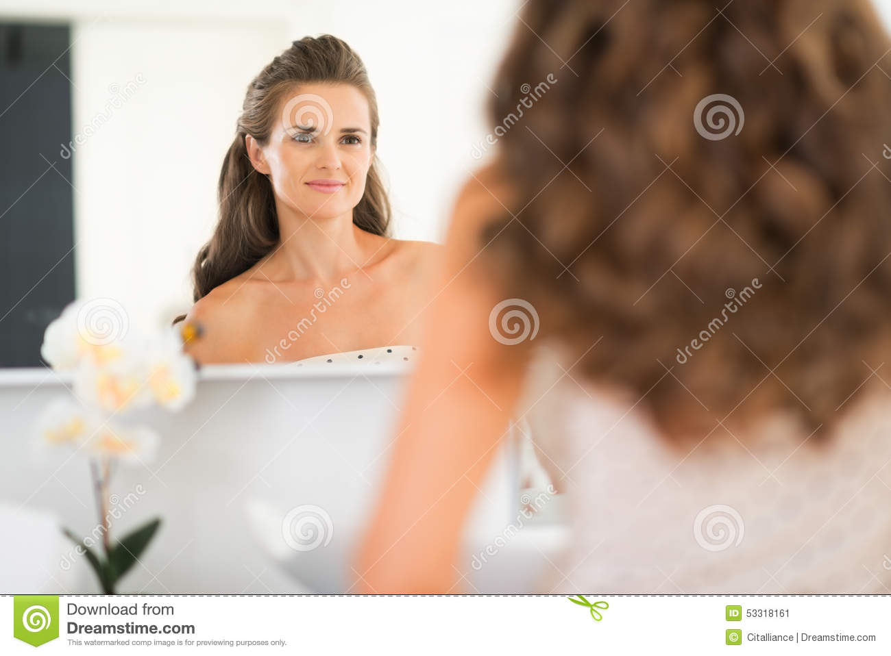 Young woman looking in mirror in bathroom
