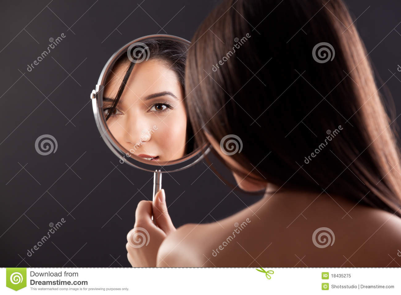 Young woman looking into a mirror, smiling.