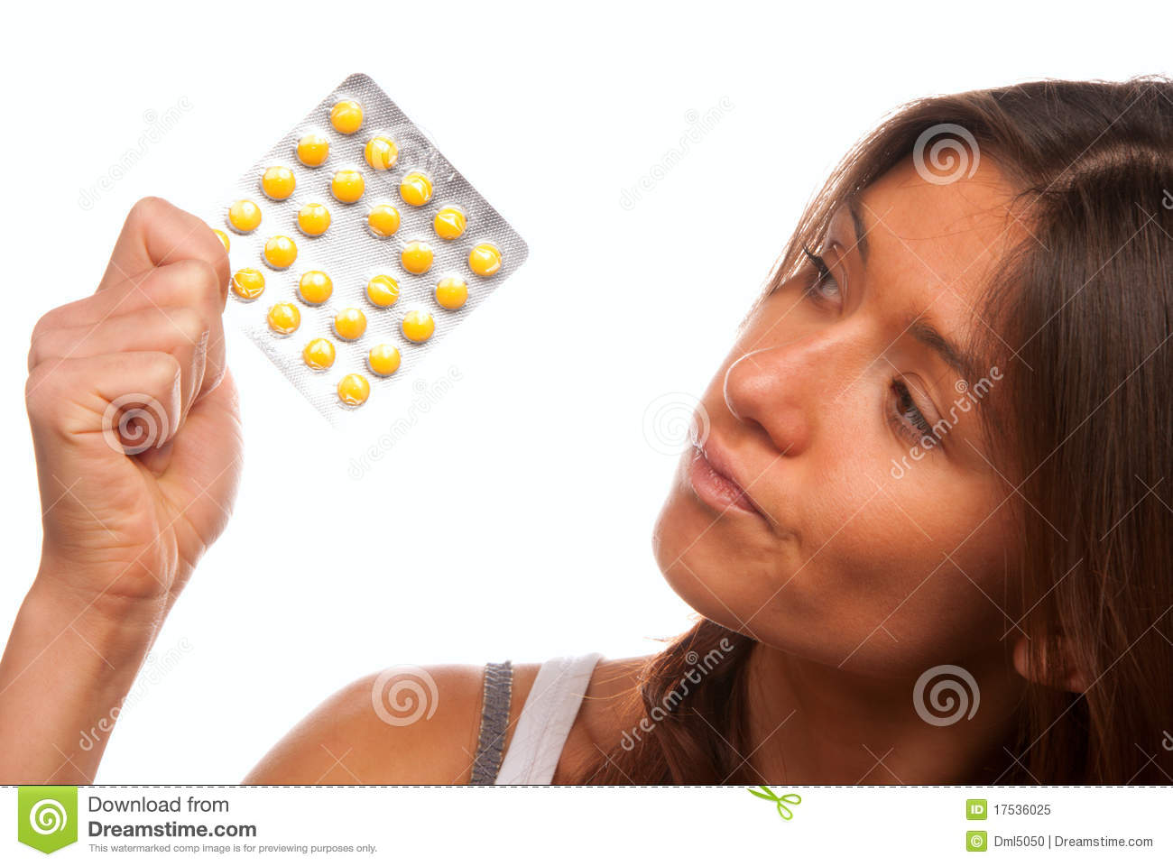 Young woman looking at yellow tablet pills