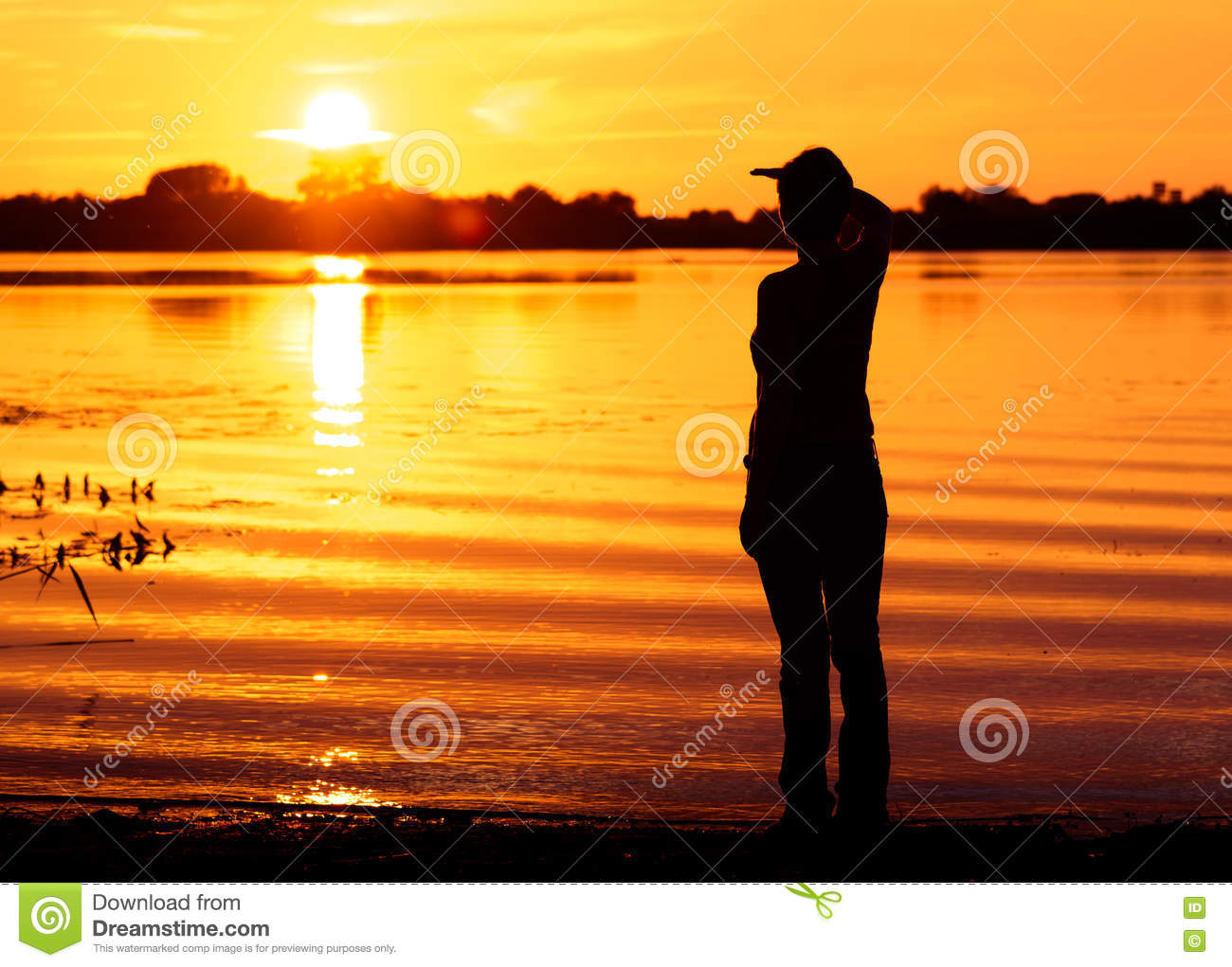 Young Woman Looks Into Distance Waiting For Someone At Sunset Stock