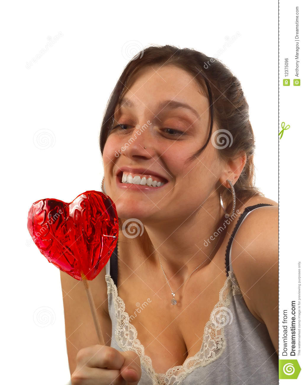 Young woman looks at heart shaped lollipop