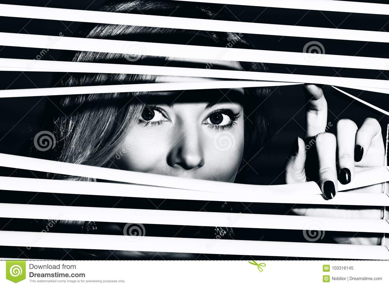 Young woman looks through the jalousie