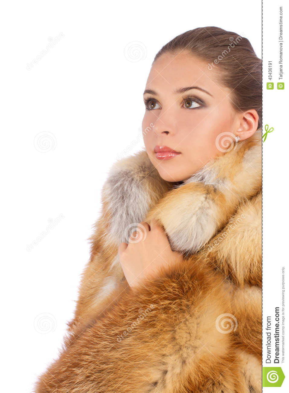 Young woman in luxury fur coat looking at the left