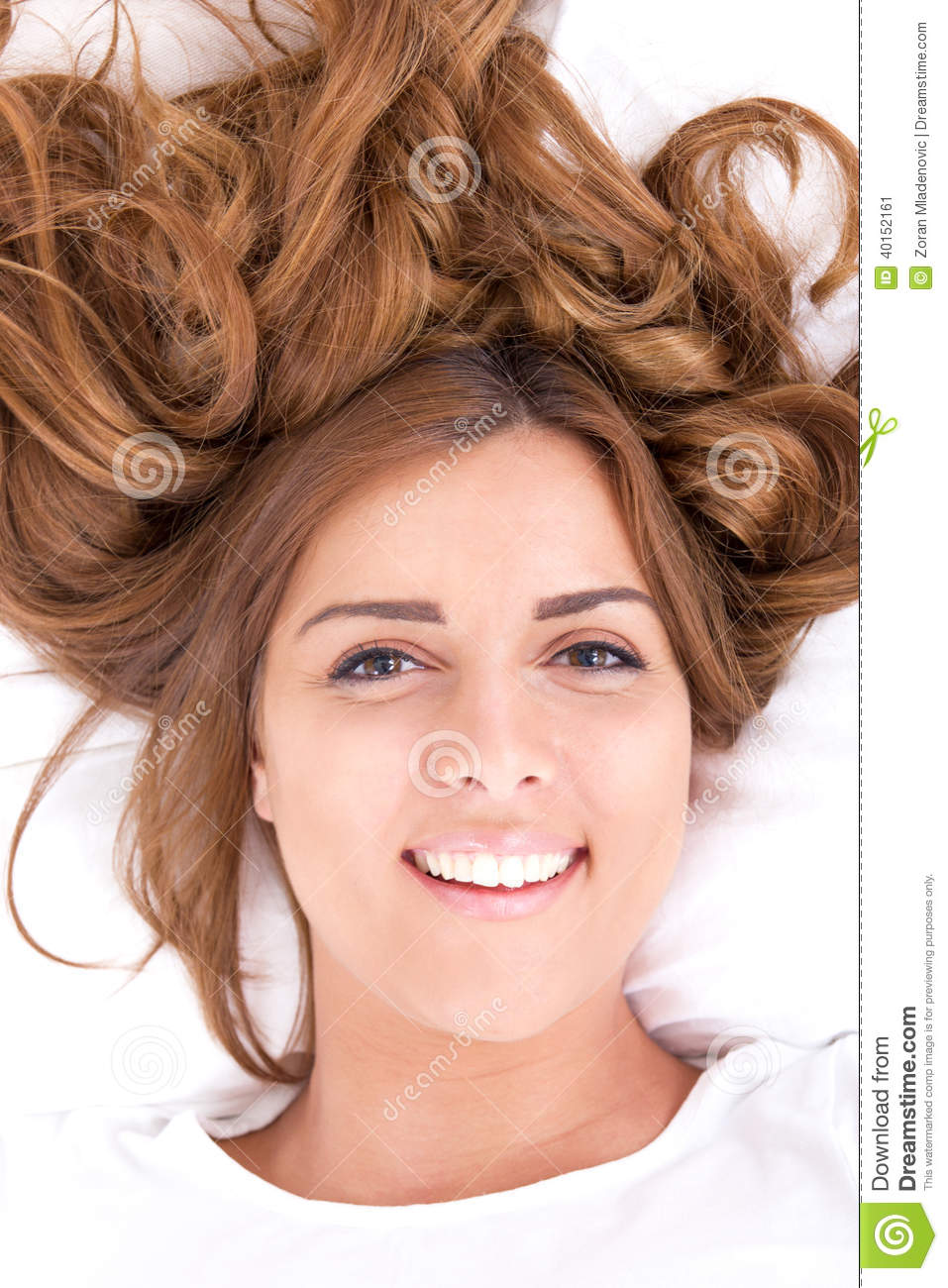 Young woman lying on bed with hair spread out