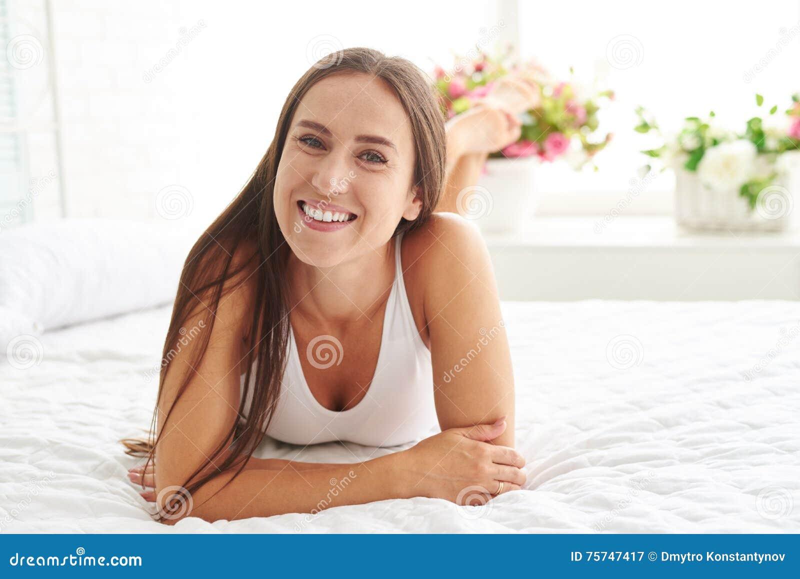 Teenage girl sitting legs crossed on bed looking in