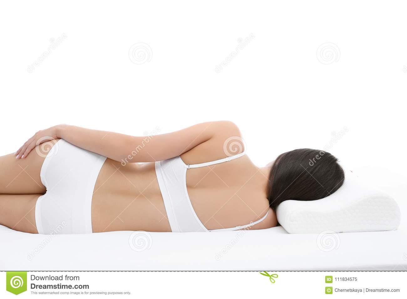 Young woman lying on bed with orthopedic pillow