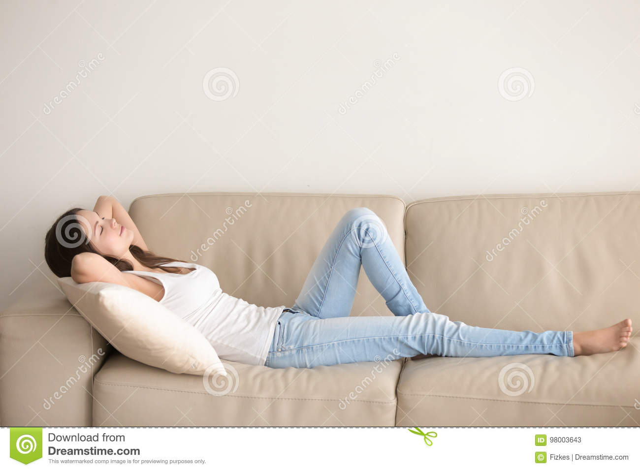 Young woman lying on couch, relaxing with hands behind head