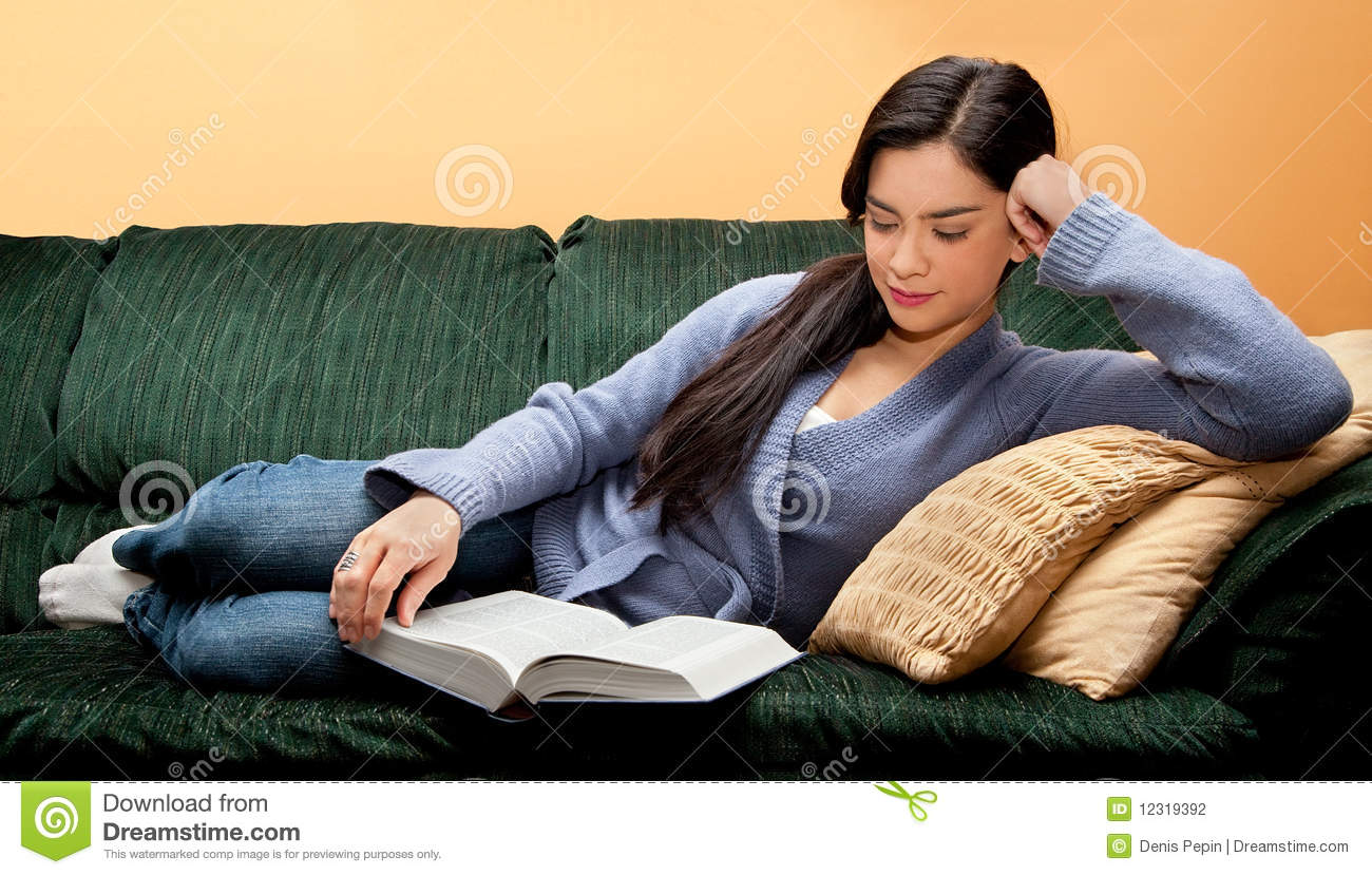 Young Woman Lying Down On Sofa And Reading Book Stock ...