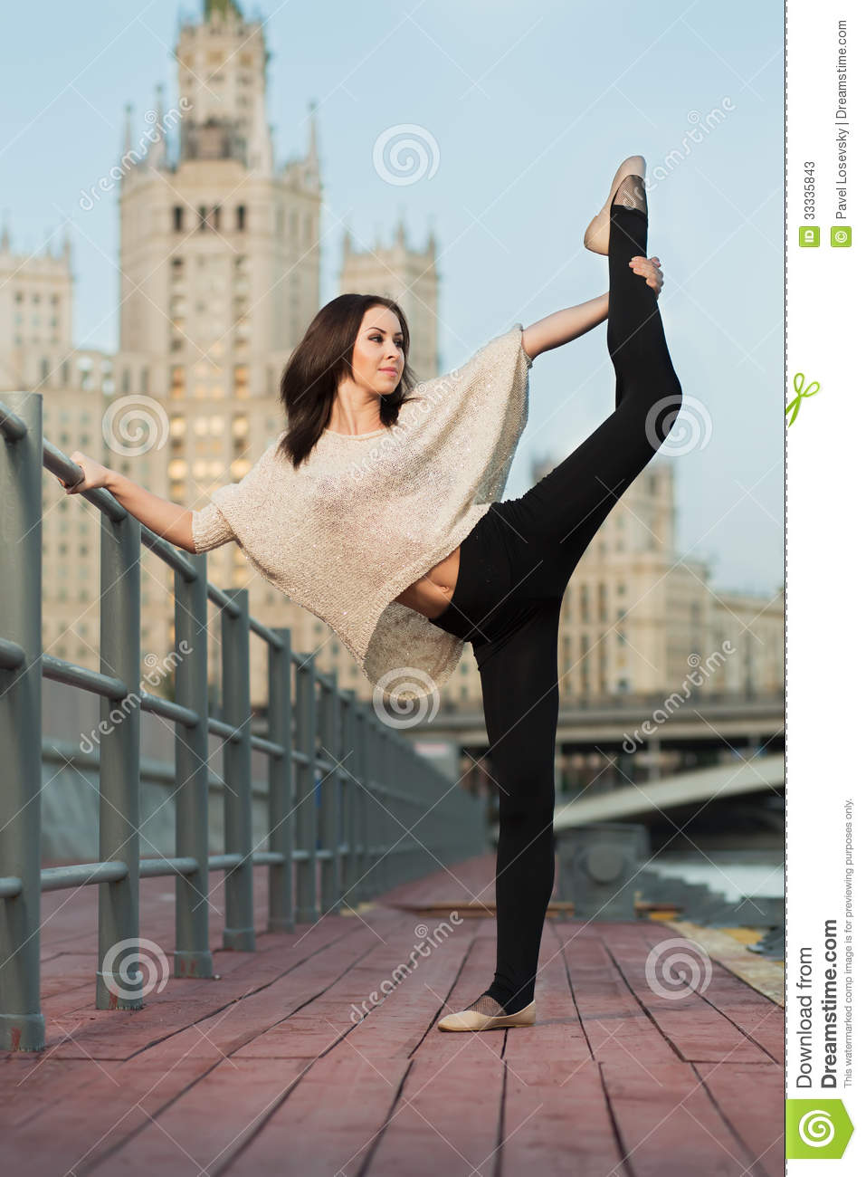 young woman makes a stretching leaning on railing stock image