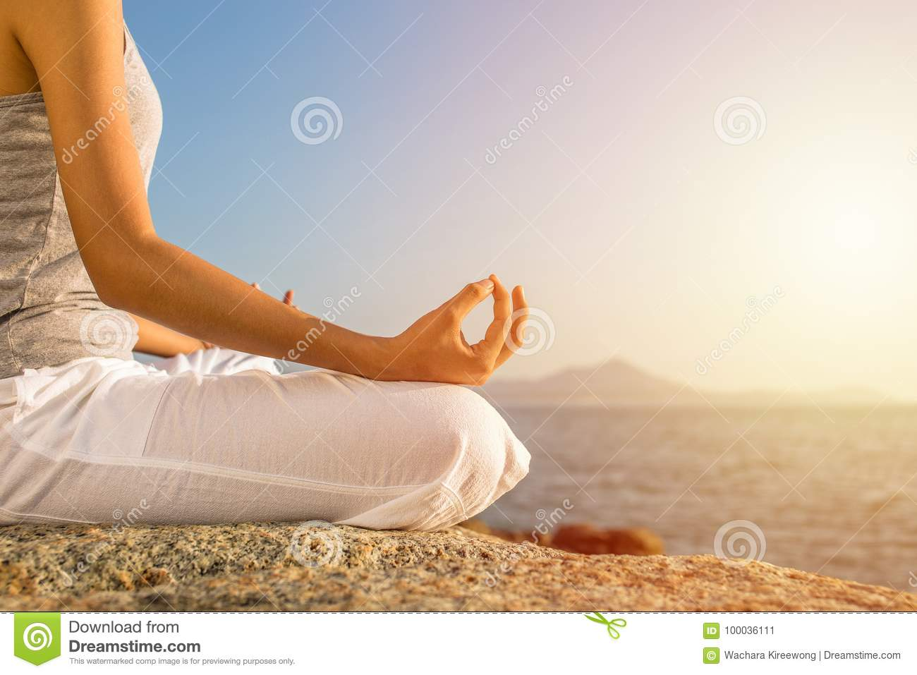 Young woman meditation yoga pose on tropical beach with sunlight