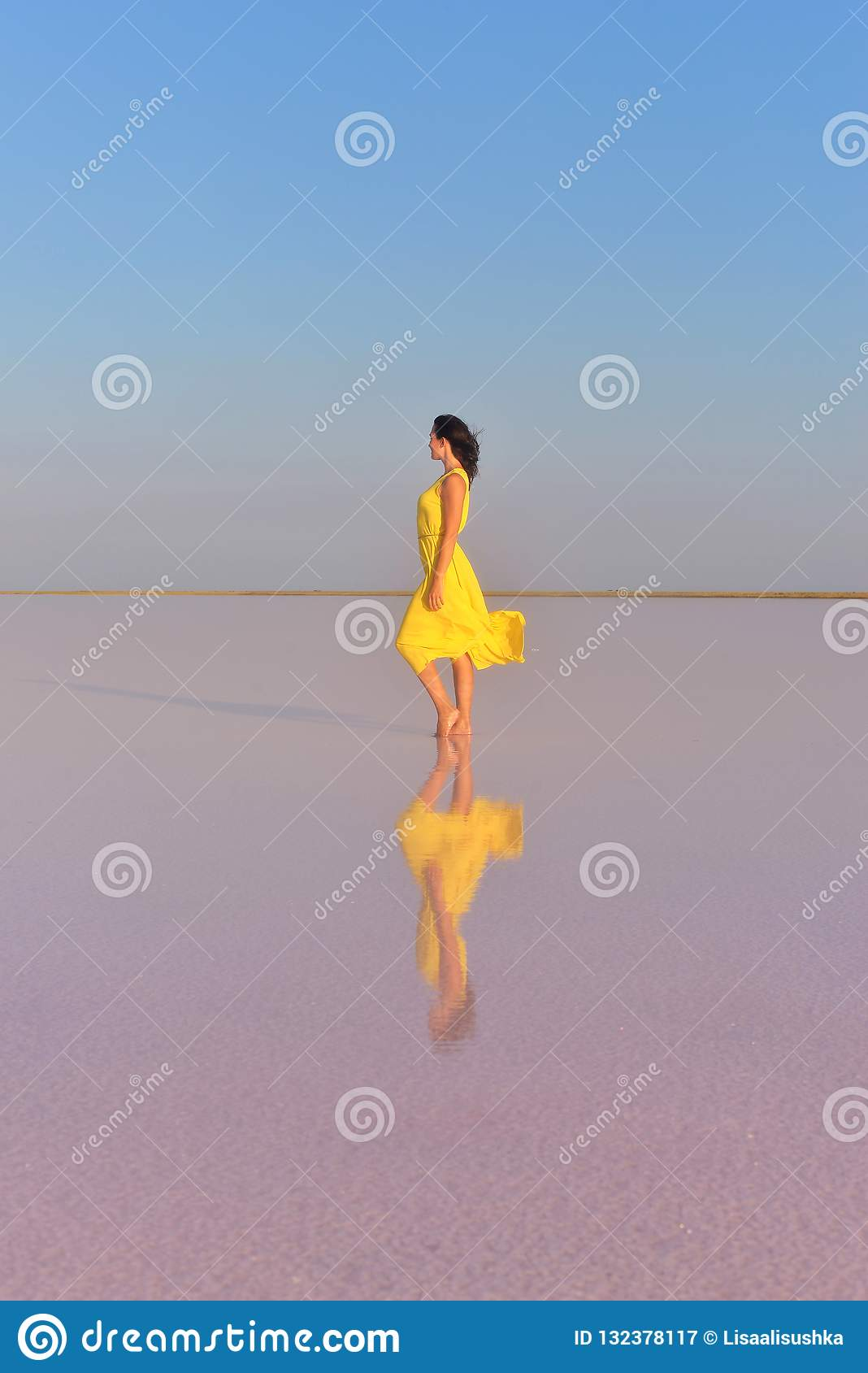 A young woman in the middle of a pink salt lake stands in a bright yellow dress and meets the sunset.