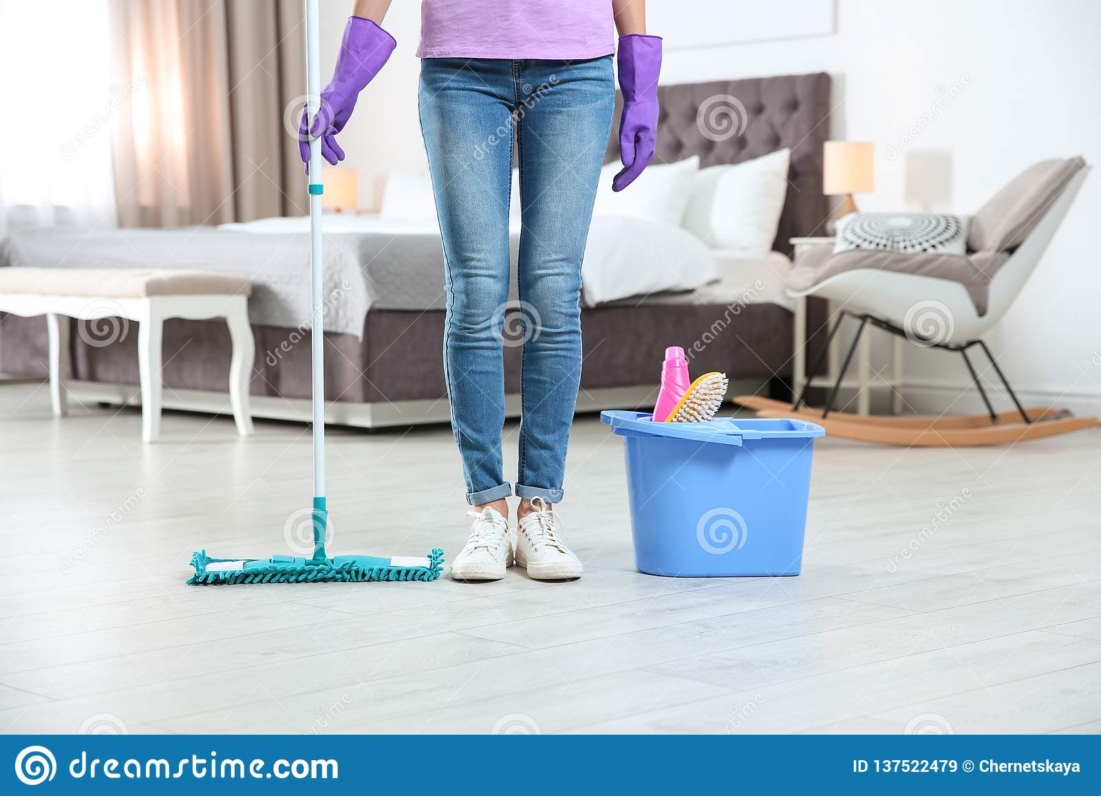 Young woman with mop and detergents in bedroom. Cleaning service
