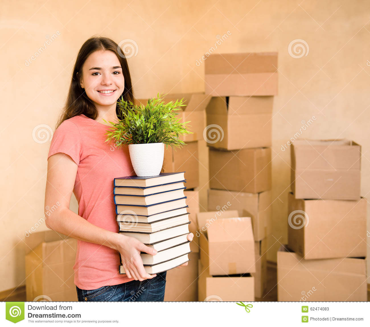 Young woman moving house to college, holding pile books and plan