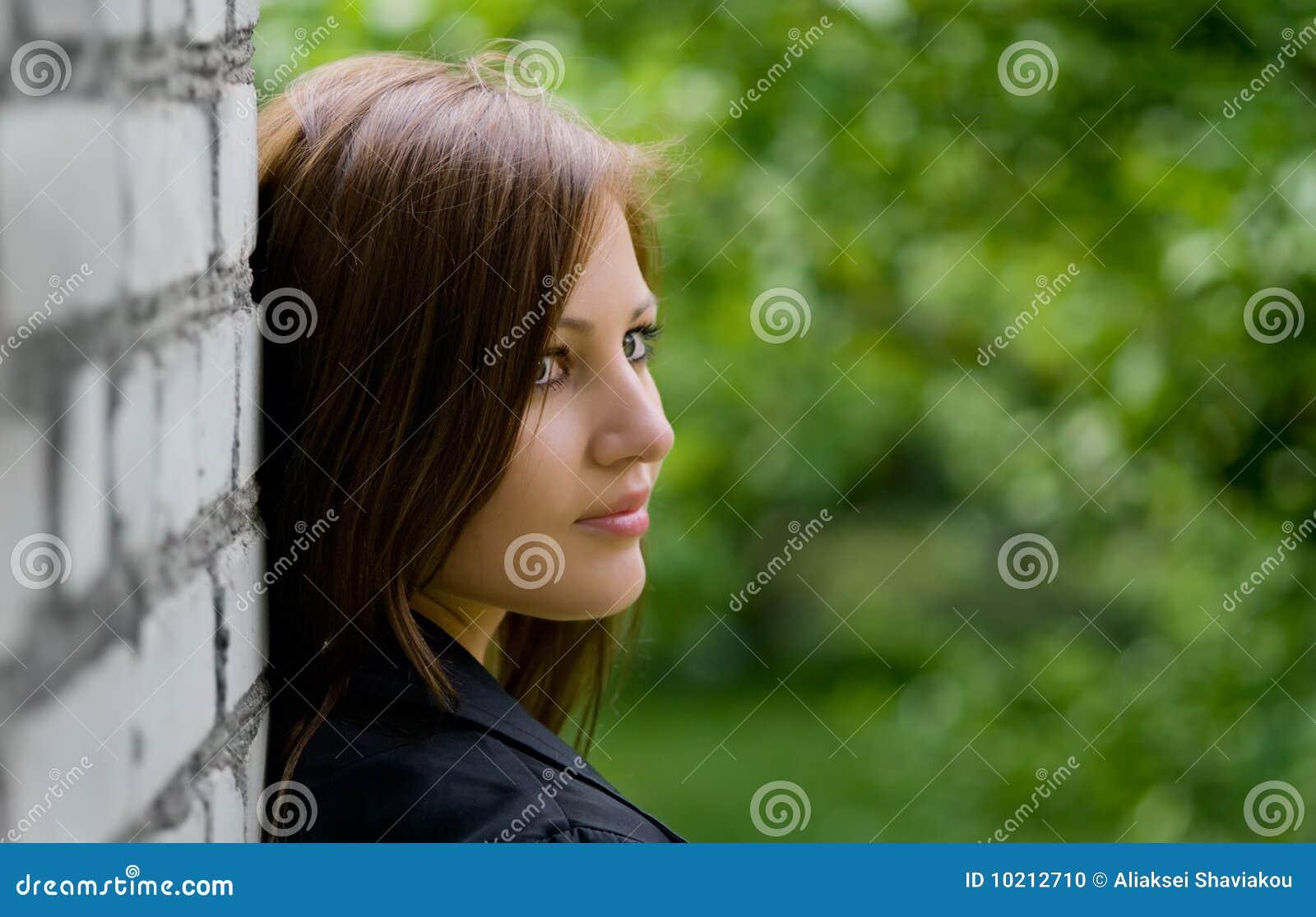 Young Woman Near Brick Wall