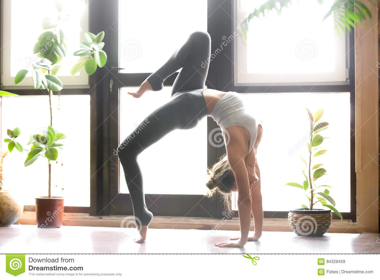 f64ca37100998 Young attractive woman practicing yoga near floor window, standing in One  legged Wheel exercise, Bridge pose, working out, wearing sportswear, grey  pants, ...