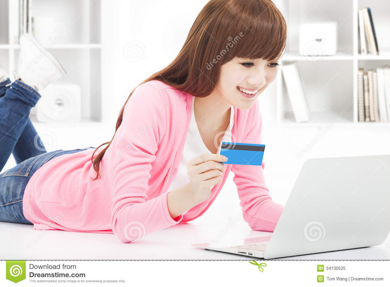 young woman online shopping at home with credit card stock