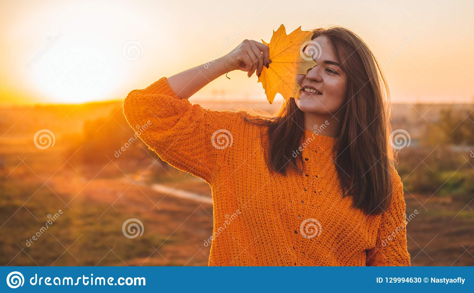 Young woman in a orange sweater with with yellow leaves, outdoor portrait in soft sunny daylight. Autumn. Sunset. Cozy