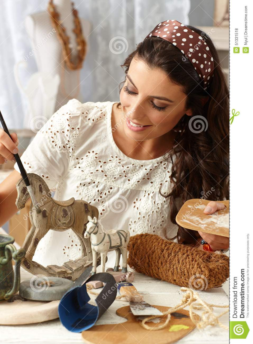 Young woman painting wooden horse