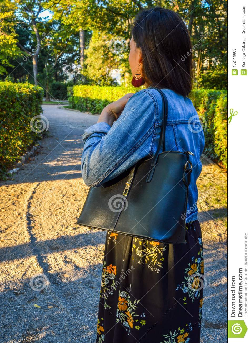 A young woman in a park, wearing a floral dress and a denim jacket, holding a black handbag